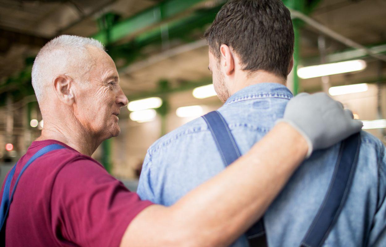Älterer Mann im Rentenalter in Arbeitskleidung und Handschuhen legt während des Gesprächs die Hand auf die Schulter einer jungen Fachkraft, wodurch Betreuung von Mitarbeitern als eine von vielen Maßnahmen gegen Fachkräftemangel gezeigt wird.