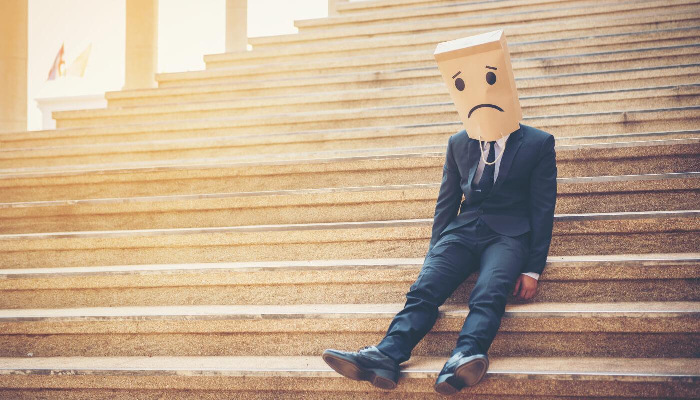 Führungskraft sitzt ausgelaugt auf Treppe und benötigt Selbstmanagement