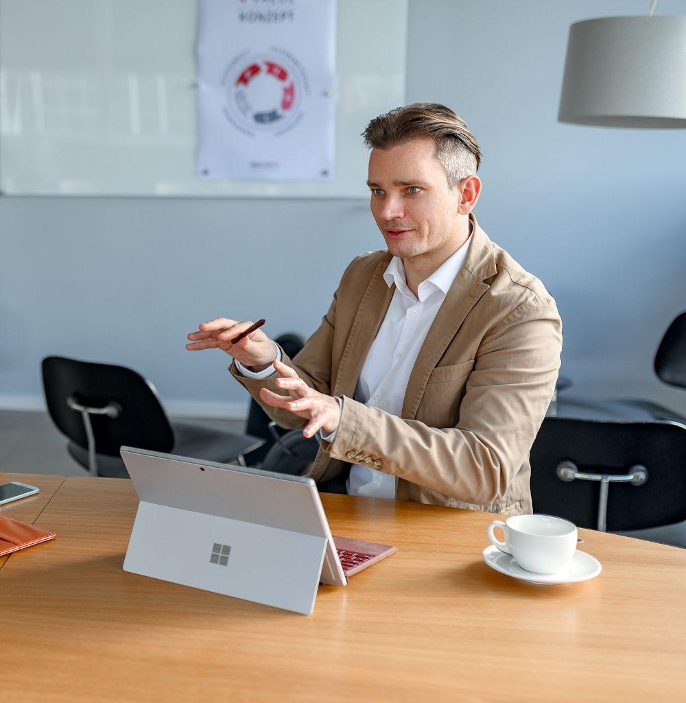 Prozessberatung und systemisches Business Coaching von Tobias Schütte sitzt mit Laptop am Tisch und berät fokussiert