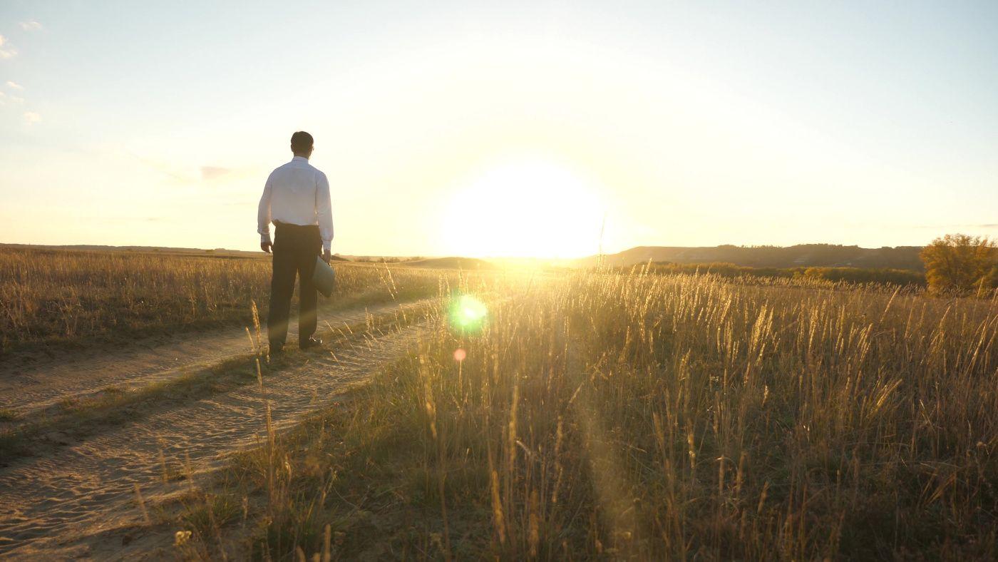 Ein Mann im Anzug geht der Sonne entgegen und signalisiert den Sinn in der Arbeit durch das Unternehmensleitbild.