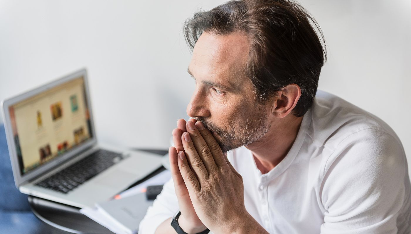 Mann sitzt in weißem Oberteil mit gefaltenen Händen vor dem Gesicht und denkt besorgt über Herausforderung wie Fachkräftemangel nach.