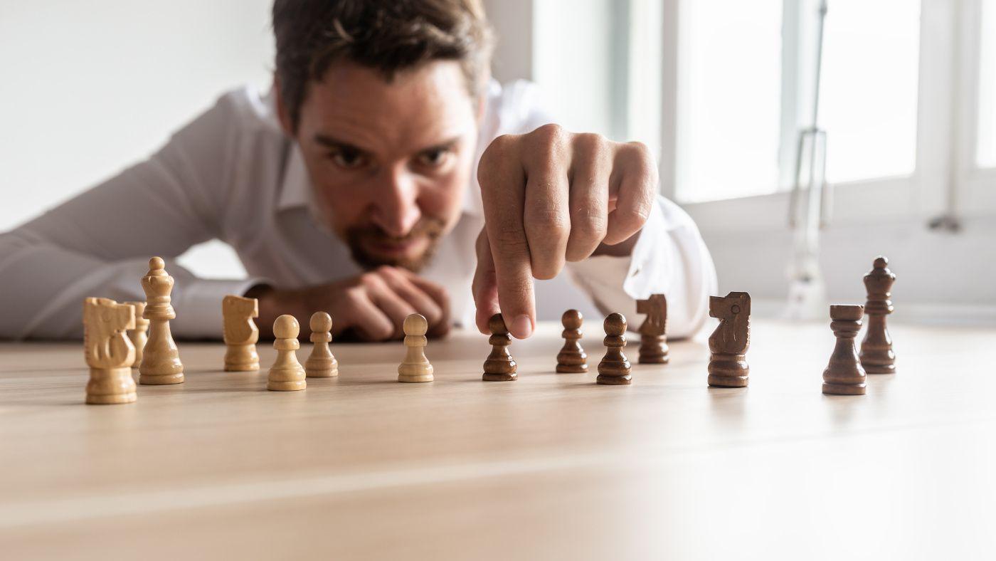 Mann mit weißen Hemd wählt auf einem Tisch stehende Schachfiguren die Maßnahmen gegen Fachkräftemangel symbolisieren.