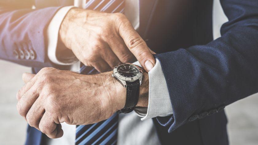 Geschäftsmann schaut auf seine Uhr und sucht nach mehr Zeit für Führung