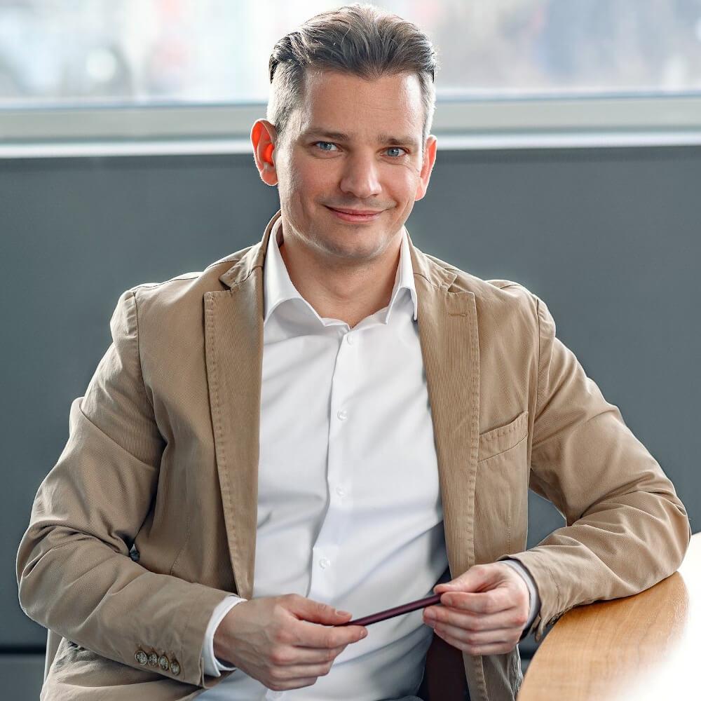 Prozessberater und systemischer Coach Tobias Schütte sitzt mit weißem Hemd und hellen Jacket aufrecht mit dem Oberkörper zum Bild gerichtet, schaut freundlich auf Sie zu und hält dabei einen Stift zwischen seinen beiden Händen.